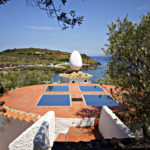 Back patio of Casa Salvador Dali with large egg statue overlooking the bay